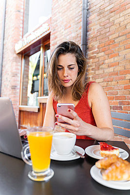 Portrait of young blogger sitting at street cafe looking at cell phone - p300m2131667 by VITTA GALLERY