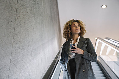 Woman holding cell phone on escalator - p300m2143463 by Hernandez and Sorokina