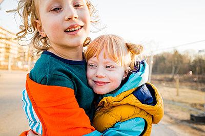 Smiling boy hugging cute sister - p300m2277318 by Irina Heß