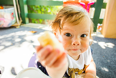 Caucasian baby girl eating on patio - p555m1411246 by Adam Hester