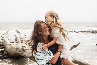 Caucasian mother hugging daughter near driftwood on beach - p555m1504318 by Marc Romanelli