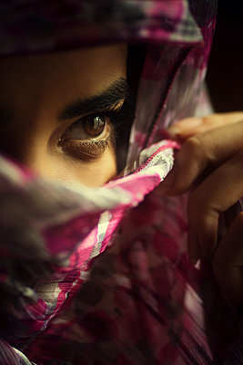 Young woman hiding face with a scarf looking away  - p794m2073050 by Mohamad Itani