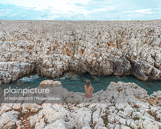 Spain, Minorca, Nude young woman in rocky landscape - p1542m2203515 by Roger Grasas