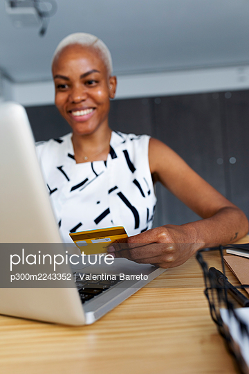 Businesswoman sitting in office using laptop to make an online payment with credit card - p300m2243352 by Valentina Barreto