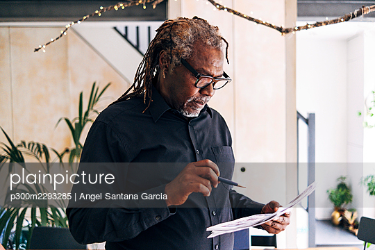 Senior male professional checking documents at home - p300m2293285 by Angel Santana Garcia