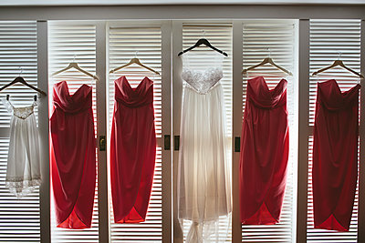A wedding dress and bridesmaids' dresses hanging on cupboard doors. - p1100m1425162 by Mint Images