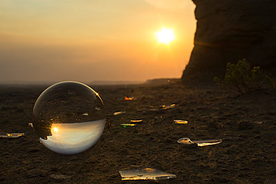 Sun shining over sea shore reflection on crystal ball during sunset - p1166m1210666 by Cavan Images