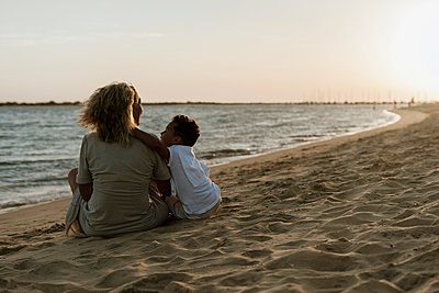 Grandmother and grandson spending leisure time at beach during sunset - p300m2220779 by Eloisa Ramos