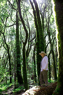 Mature man with hand in pocket standing by tree in Garajonay National Park on sunny day, La Gomera - p300m2277433 by Petra Stockhausen