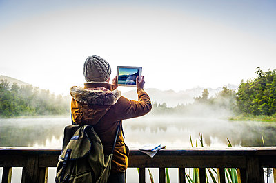 Hispanic woman photographing foggy mountain lake with digital tablet - p555m1304955 by Dave and Les Jacobs