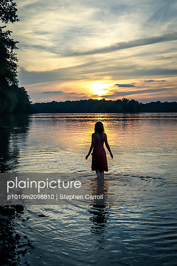 Sunset, Woman in river, rear view - p1019m2098810 by Stephen Carroll