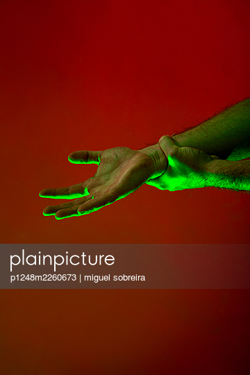 Green illuminated hands against red background - p1248m2260673 by miguel sobreira