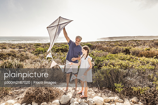 Father and daughter with kite in dunes - p300m2167020 by Floco Images