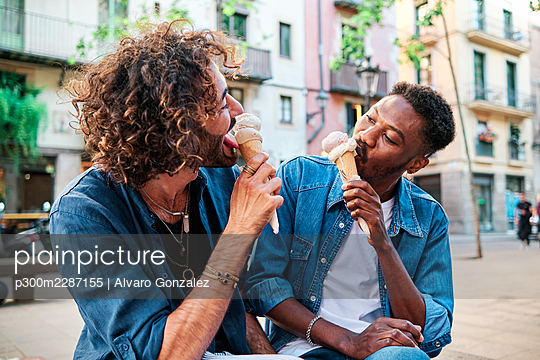 Gay couple eating ice cream while looking at each other - p300m2287155 by Alvaro Gonzalez