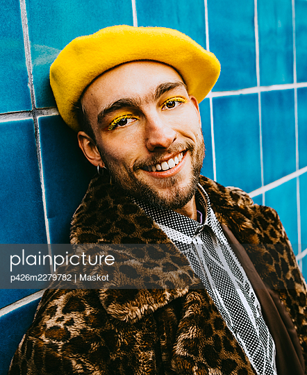 Portrait of smiling young man wearing yellow beret against blue tiled wall - p426m2279782 by Maskot