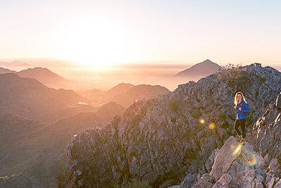 Hiker standing at Piestewa Peak against clear sky during sunrise - p1166m1488843 by Cavan Images
