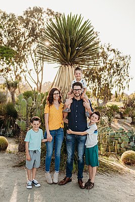 Portrait of family smiling at camera in sunny cactus garden - p1166m2136629 by Cavan Images