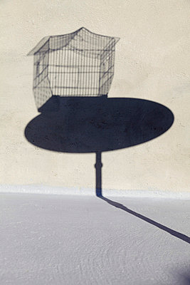 Shadow of empty birdcage on a little round table - p2651439 by Oote Boe