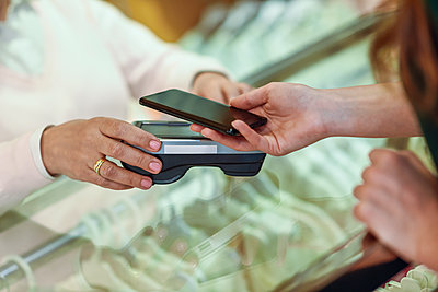 Close-up of woman paying with smartphone in a store - p300m2012651 von Javier Sánchez Mingorance