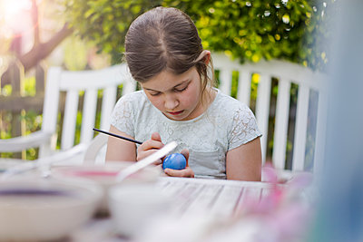 Girl painting Easter egg on garden table - p300m2114788 by Robijn Page