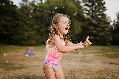 Happy girl playing with soap bubbles in garden - p300m2206985 by Sara Monika
