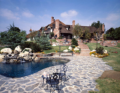 Large cottage with pond and stone walkway - p5551474f by Blend Images