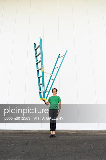 Acrobat balancing ladder upside down in his hand - p300m2012369 von VITTA GALLERY