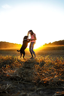 Teenage Girl and her Dog at sunset - p1019m1487241 by Stephen Carroll