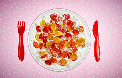 Plate of candies and red plastic cutlery on pink cloth - p300m1028722f by Kai Schwabe