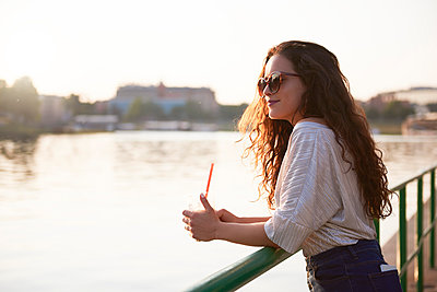 Smiling young woman with a takeaway drink enjoying the sunset at the riverside - p300m2012218 by gpointstudio