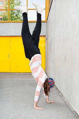 Teenage girl doing handstand, Stockholm, Sweden - p312m897160 by Johner