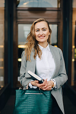 Portrait of smiling businesswoman with book and bag standing by store in city - p426m2186673 by Maskot