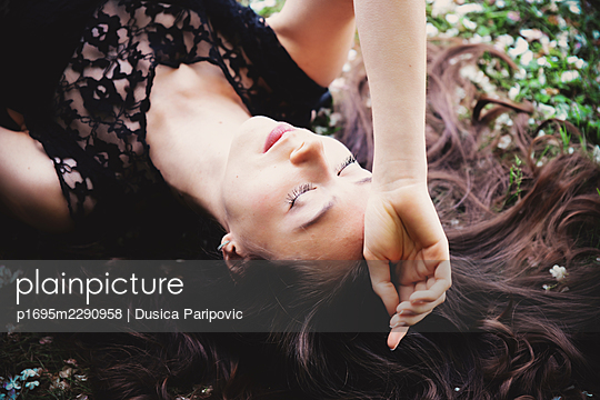 Young woman with closed eyes lies on the back - p1695m2290958 by Dusica Paripovic