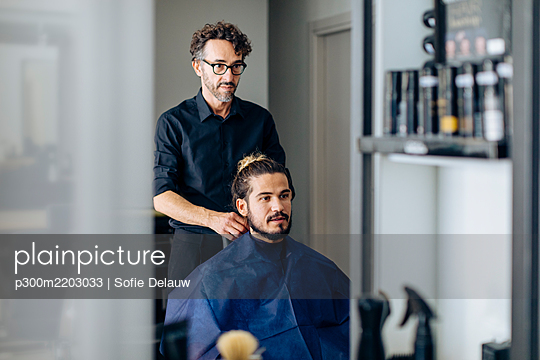 Hairdresser styling man's hair at salon - p300m2203033 by Sofie Delauw