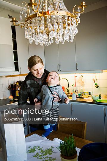 Mother and baby boy (6-11 months) in domestic kitchen - p352m2119589 by Lena Katarina Johansson