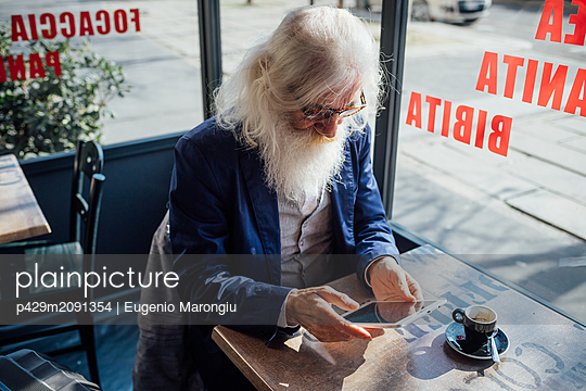 Senior businessman using digital tablet in cafe, Milano, Lombardia, Italy - p429m2091354 by Eugenio Marongiu