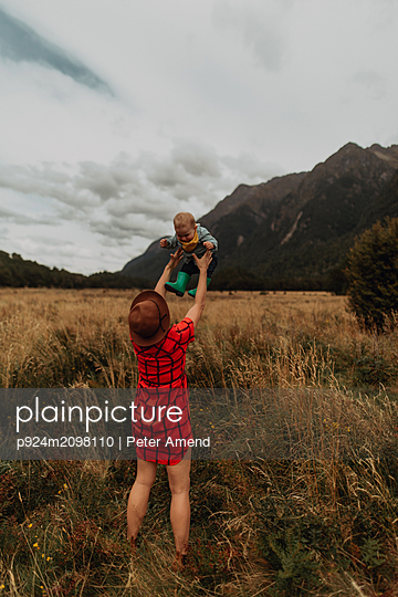Mother playing with baby in wilderness, Queenstown, Canterbury, New Zealand - p924m2098110 by Peter Amend