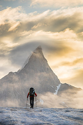 Backpacker hiking towards Mt. Loki, Baffin Island, Canada. - p1166m2189688 by Cavan Images