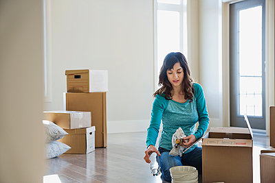 Woman unpacking cardboard boxes in new home - p1192m1043476f by Hero Images