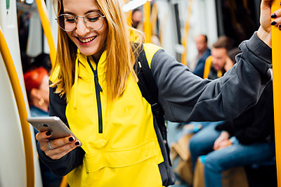 Smiling young woman standing in underground train using her smartphone - p300m2143835 by Jose Luis CARRASCOSA