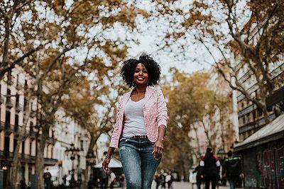 Carefree woman walking on street in city - p300m2240608 by Gala Martínez López