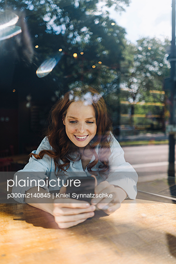 Happy redheaded woman with cell phone in a cafe - p300m2140845 by Kniel Synnatzschke
