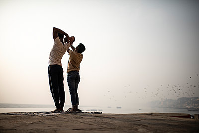 Two men practicing yoga in the morning light - p1007m2099030 by Tilby Vattard