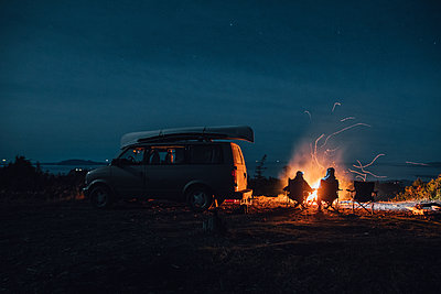 Canada, British Columbia, Prince Rupert, two men sitting at camp fire at minivan at night - p300m1568042 by Gustafsson