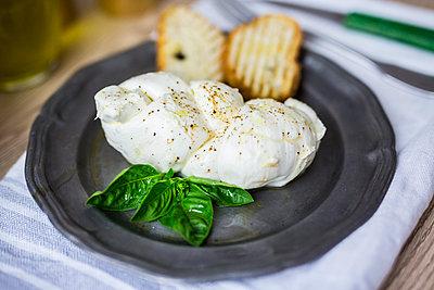 Mozzarella braid, basil and bread on plate - p300m2029176 by Giorgio Fochesato