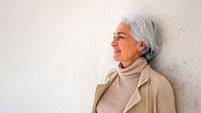 Smiling woman with short hair day dreaming in front of white wall - p300m2281465 by PICUA ESTUDIO