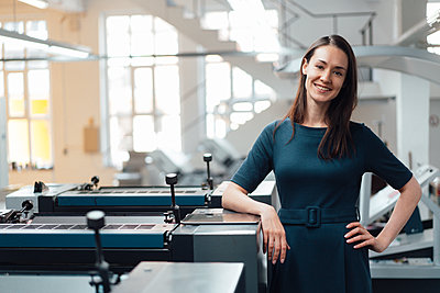 Smiling businesswoman standing with hand on hip in industry - p300m2300270 by Kniel Synnatzschke