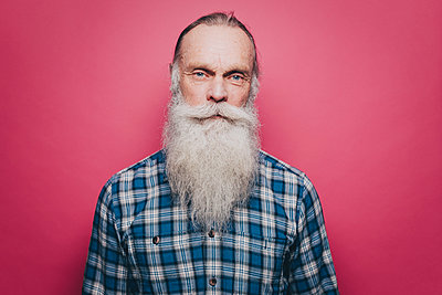 Portrait of confident senior man with long white beard against pink background - p426m1588490 by Maskot