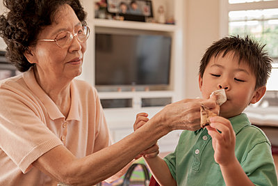 Asian grandmother wiping face of grandson at table - p555m1408700 by Shestock