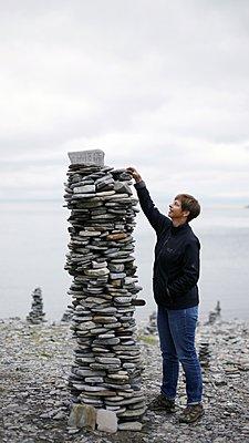 Woman making a cairn. - p896m1479461 by Richard Brocken